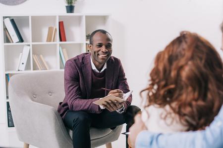 Photo pour Smiling african american psychiatrist talking to young couple - image libre de droit