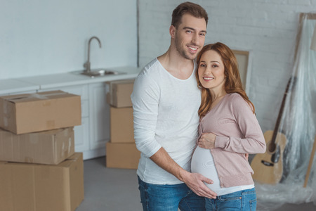 Foto de happy pregnant couple smiling at camera in new house - Imagen libre de derechos