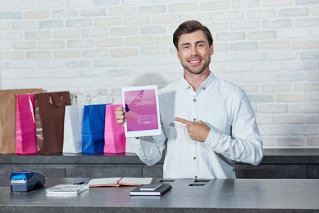 Handsome young salesman pointing at digital tablet with online shopping application and smiling at camera in store