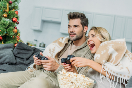 Foto de Happy young couple with popcorn playing video games together on couch at home - Imagen libre de derechos