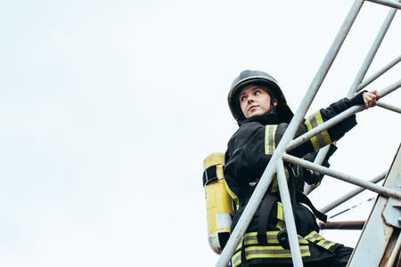 Photo pour female firefighter in protective uniform and helmet with fire extinguisher on back standing on ladder with blue sky on background - image libre de droit