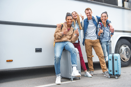 Photo pour Smiling multiethnic friends with wheeled bags doing thumbs up and peace gestures near travel bus - image libre de droit
