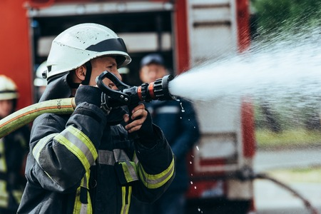Photo for Selective focus of firefighter with water hose extinguishing fire on street - Royalty Free Image