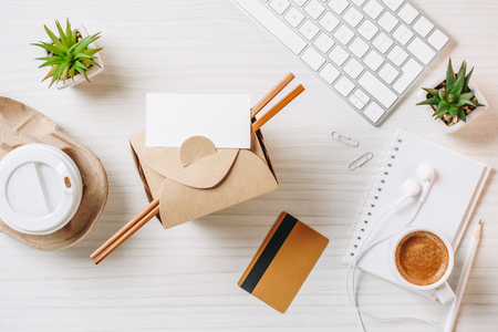 Foto de Top view of empty business card, credit card, wok box, paper coffee cup at table in office - Imagen libre de derechos
