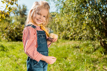 Photo for Little kid holding adorable yellow baby chick and looking at camera outdoors - Royalty Free Image