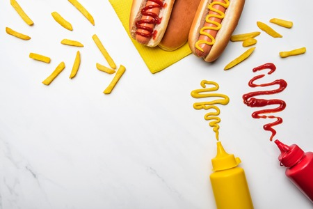 Photo pour Top view of hot dogs with mustard and ketchup on white marble surface - image libre de droit