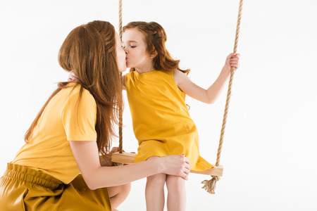 Foto de Daughter sitting on swing and kissing mother isolated on white background - Imagen libre de derechos