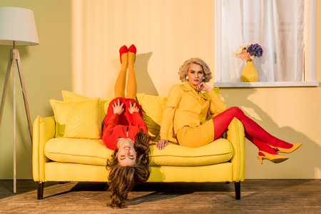 Foto de Retro styled beautiful girls in red and yellow dresses on sofa at home - Imagen libre de derechos