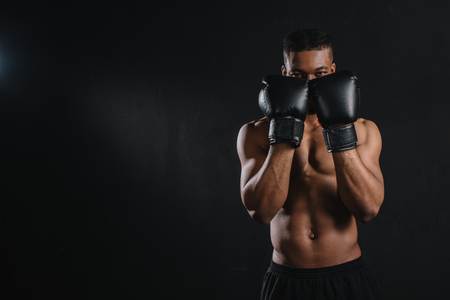 Photo for Young shirtless African American boxer in boxing gloves looking at camera isolated on black background - Royalty Free Image