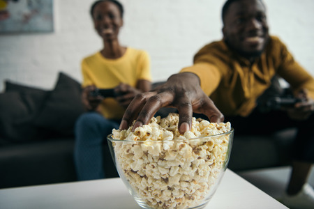 Close-up view of young African American couple eating popcorn and playing with joysticks at home