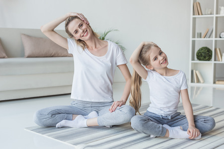 Foto de Mother and daughter stretching neck before exercising at home - Imagen libre de derechos