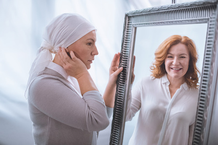 Foto de Upset sick mature woman in kerchief looking at smiling reflection in mirror, cancer concept - Imagen libre de derechos