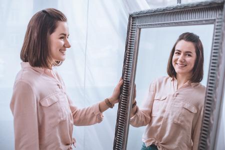 Foto de Beautiful smiling young woman standing near mirror and looking at reflection - Imagen libre de derechos