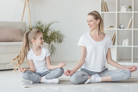 Photo pour Happy mother and daughter sitting in lotus pose at home together - image libre de droit