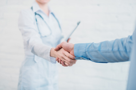 Photo pour Cropped shot of doctor shaking hands of patient patient - image libre de droit