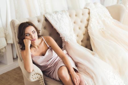 Foto de Bored woman sitting on sofa in wedding fashion shop - Imagen libre de derechos