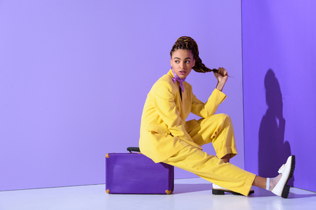 Photo for African American girl posing in yellow suit sitting on purple suitcase, on trendy ultra violet background - Royalty Free Image