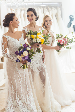 Photo pour Smiling women in wedding dresses with flowers in wedding atelier - image libre de droit