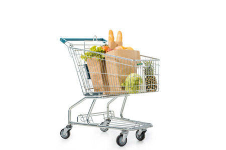 Foto de paper bags full of products in shopping trolley isolated on white - Imagen libre de derechos
