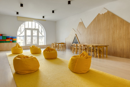 Foto de yellow bean bag chairs and wooden tables in kindergarten playing room - Imagen libre de derechos