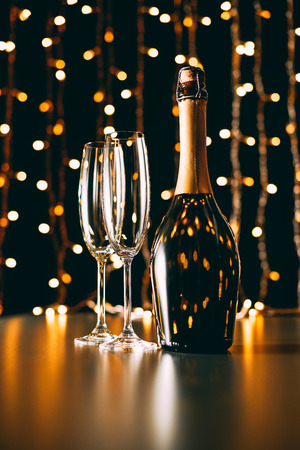 Photo for champagne bottle and glasses on garland light background, christmas concept - Royalty Free Image