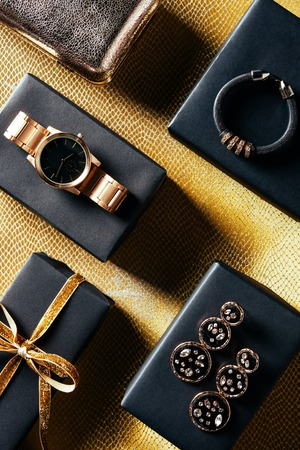 Foto per flat lay with wrapped gift, feminine jewelry and purse on golden backdrop - Immagine Royalty Free