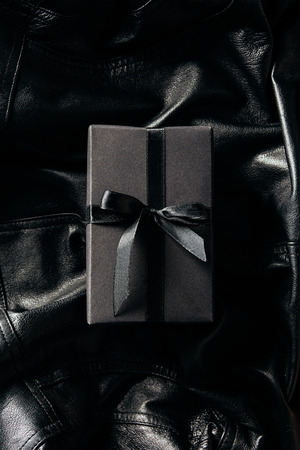 Foto de top view of black wrapped gift on black leather jacket background - Imagen libre de derechos