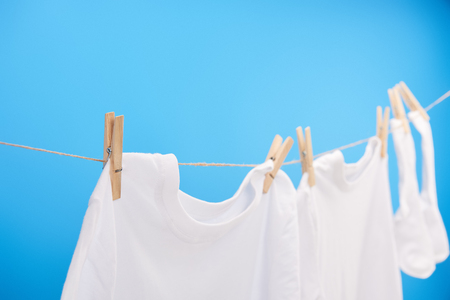 Foto de close-up view of clean white t-shirts and socks hanging on clothesline isolated on blue - Imagen libre de derechos