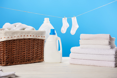 Photo for laundry basket, plastic containers with laundry liquids, pile of clean soft towels and white socks hanging on rope on blue - Royalty Free Image