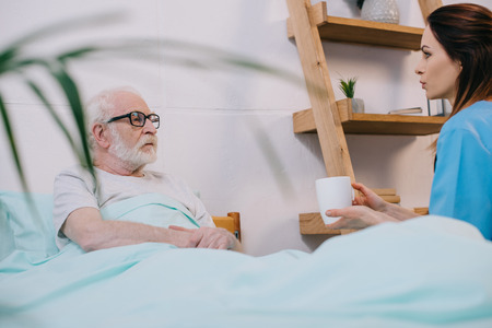 Nurse giving cup with drink to senior patient in bed