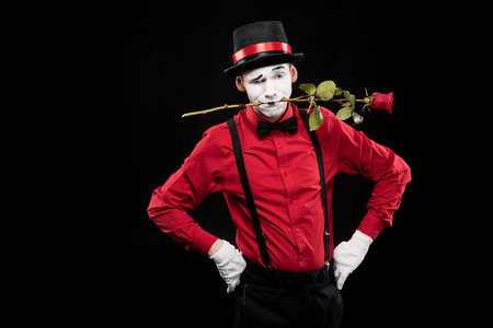 Photo for mime grimacing and holding red rose in mouth isolated on black - Royalty Free Image