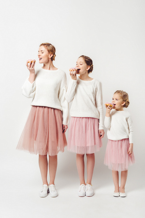 Foto de family in similar clothing eating sweet doughnuts isolated on grey - Imagen libre de derechos