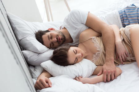 Photo pour young couple in pajamas sleeping in bed together - image libre de droit