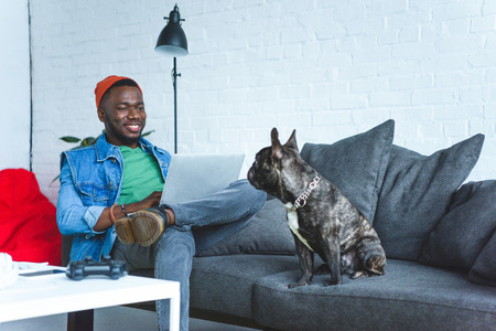 Photo for Young man working on laptop while sitting on sofa with bulldog - Royalty Free Image