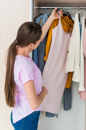 Photo pour attractive young woman choosing clothes from rack - image libre de droit