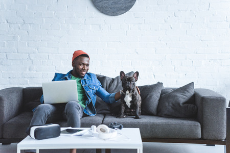 Photo pour African american man working on laptop and hugging French bulldog by table with modern gadgets - image libre de droit
