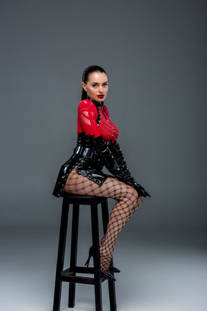 Kinky woman in sexy costume posing on high chair on grey background
