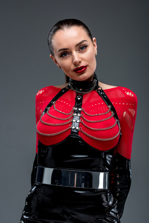 Seductive young woman in leather costume isolated on grey