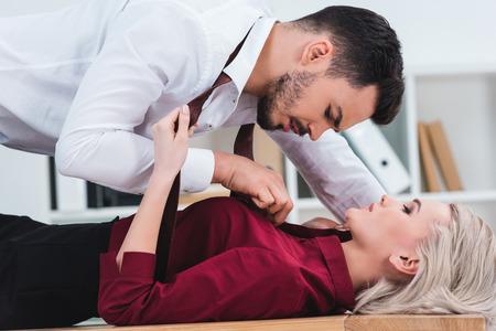 Foto de side view of businessman unbuttoning shirt of young businesswoman at workplace - Imagen libre de derechos