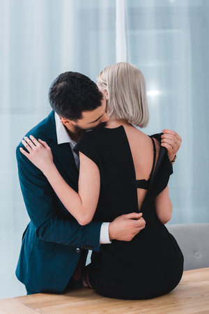 Photo pour businessman taking off black dress from sexy female colleague in office - image libre de droit