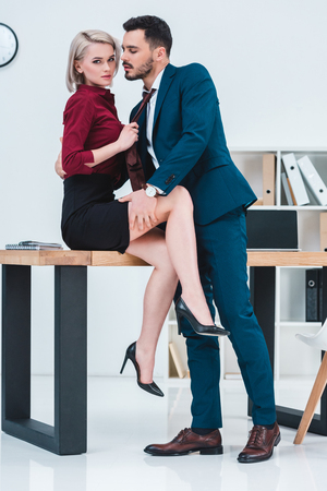 Photo pour sexy young couple of business people flirting in office - image libre de droit