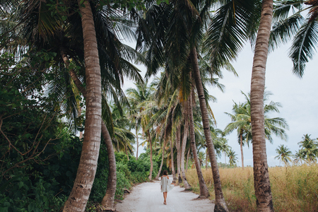 Photo pour back view of girl walking between palm trees at Ukulhas island, Maldives - image libre de droit