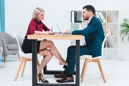 Foto de side view of young couple of business people looking at each other while working together and flirting under table in office - Imagen libre de derechos