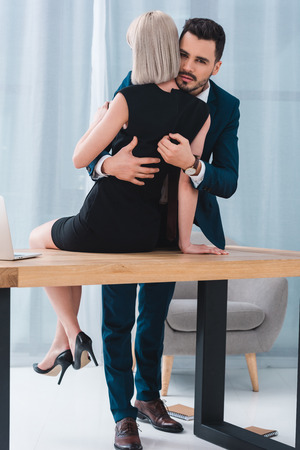 Photo pour businessman and businesswoman hugging in foreplay at workplace - image libre de droit