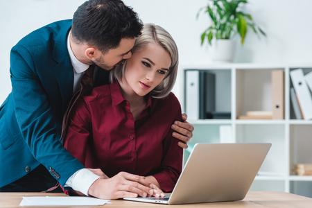 Photo pour businessman flirting with beautiful female colleague using laptop in office - image libre de droit