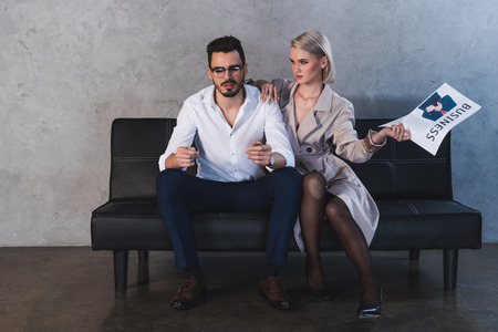 Photo pour sexy girl in coat and stockings holding newspaper and flirting with handsome businessman - image libre de droit