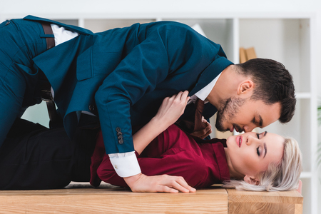 Photo pour side view of sexy young couple kissing on table in office - image libre de droit