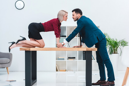 Photo pour side view of seductive young couple looking at each other while flirting in office - image libre de droit