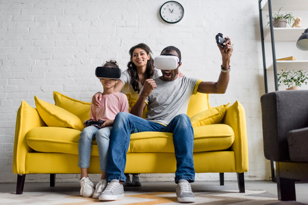 excited father and daughter playing video games while mother sitting behind and watching