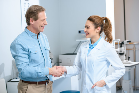 Photo pour middle aged man shaking hands with female doctor after consultation in clinic - image libre de droit